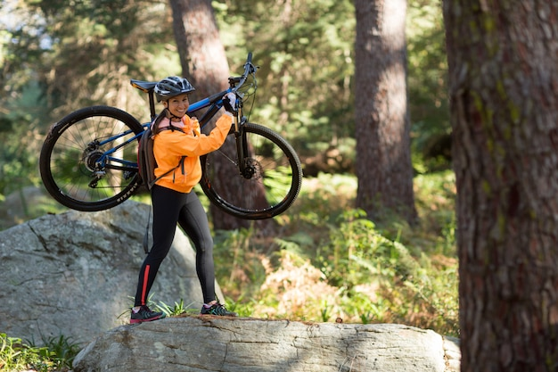 Female biker holding mountain bike and walking in forest