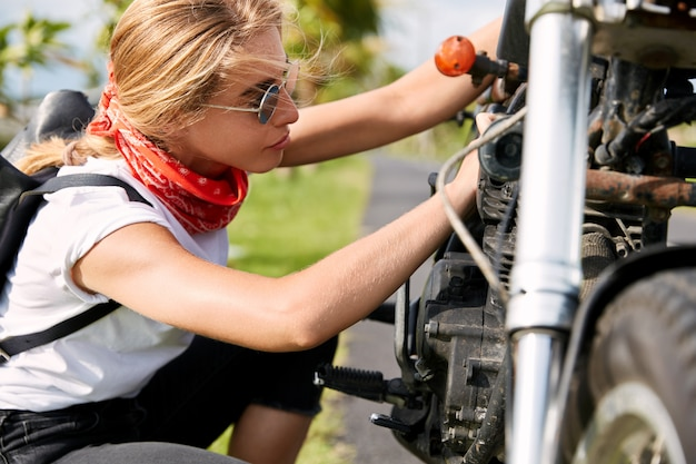 Женский байкер, ремонтирующий мотоцикл