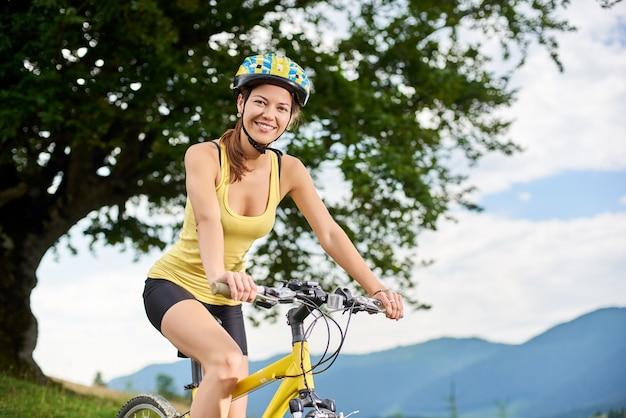Female biker riding on yellow mountain bicycle