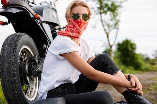 Женщина-байкер сидит рядом с мотоциклом
