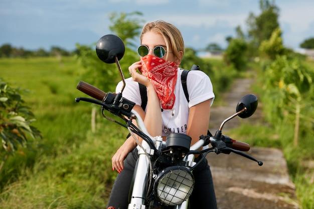 バイクの隣に座っている女性のバイカー