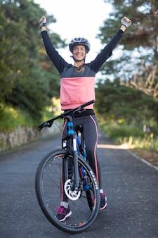 Женский байкер, стоя с горным велосипедом в сельской местности