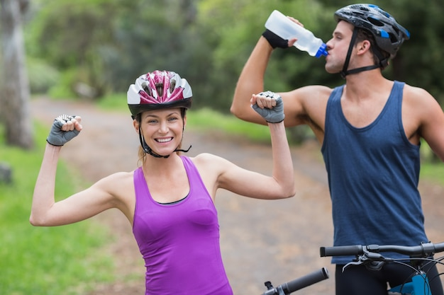 Female biker with man drinking water in forest