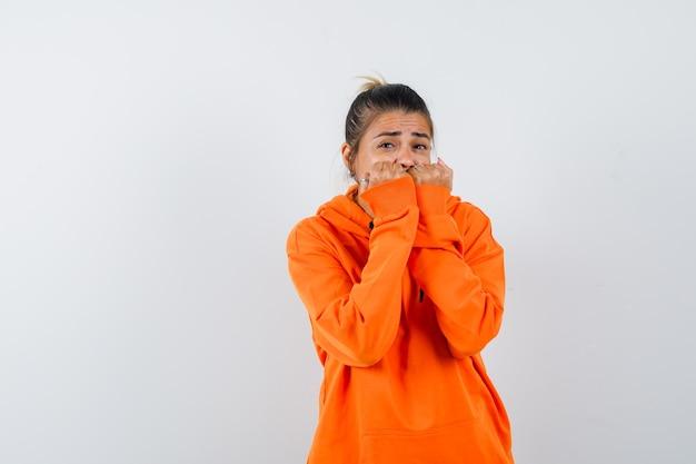 Женщина в оранжевой толстовке с капюшоном эмоционально кусает кулаки и выглядит испуганной