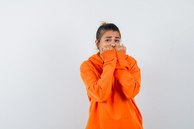 Female biting fists emotionally in orange hoodie and looking frightened
