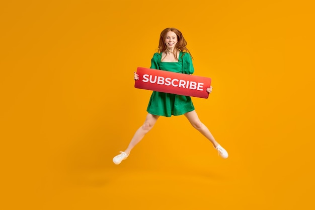 Female blogger asks to subscribe to channel for video vlogs redhead lady in green dress emotionally ...