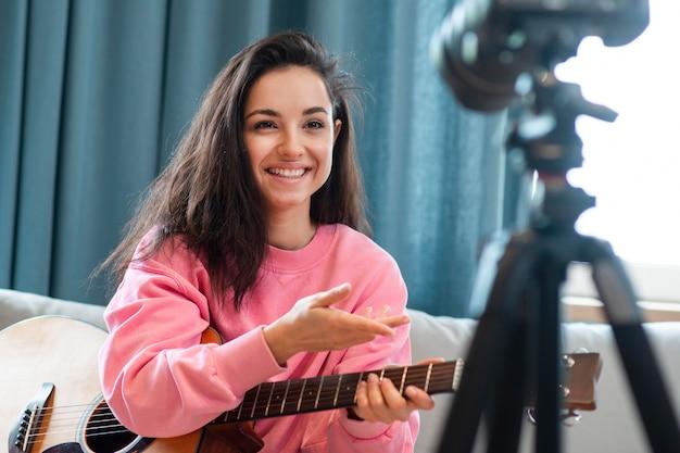 Женский блоггер держа гитару и смотря камеру