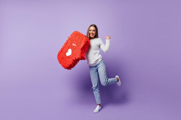 미소로 춤을 추는 좋은 분위기의 여성 블로거. 행복한 감정을 표현하는 흰색 스웨터에 놀라운 아가씨의 실내 초상화.