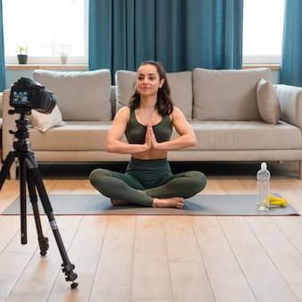 Женский блоггер в спортивной одежде делает позу лотоса