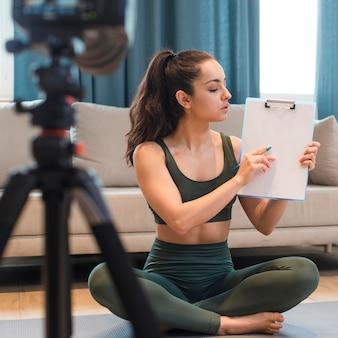 Женский блоггер в спортивной одежде показывает буфер обмена