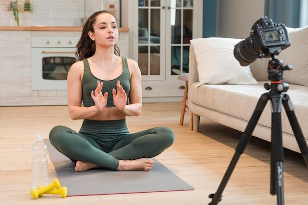 Женский блоггер в спортивной одежде, сидя на коврик для йоги