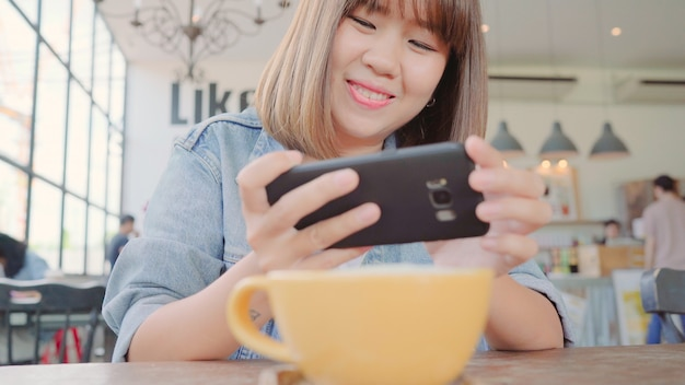 Female blogger photographing green tea cup in cafe with her phone.