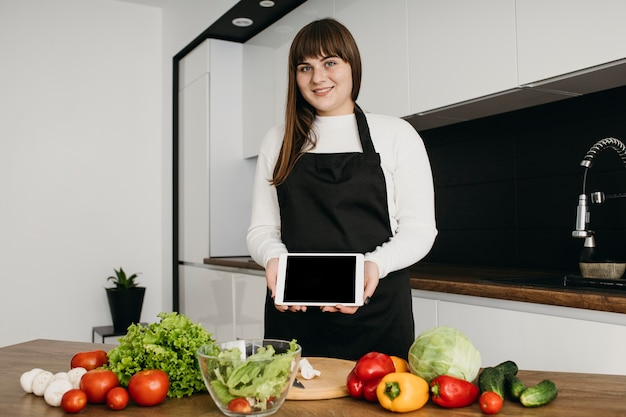 Female blogger recording herself while preparing salad with tablet