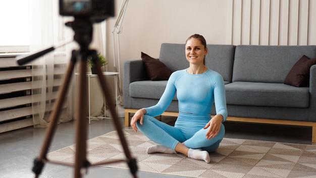 집에서 스포츠 비디오를 녹화하는 여성 블로거. 요가 포즈를 한 여성이 온라인 코스의 비디오를 녹화하고 있습니다. 집에서 혼자서 운동하기.
