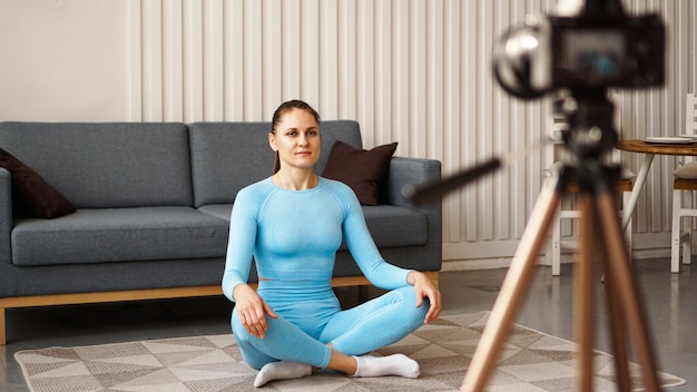 Female blogger recording sports video at home. a woman in a yoga pose is recording video for an online course. doing sports on your own at home.