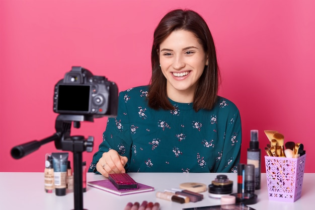 Female blogger sits at table with lots cosmetics products, records tutorial video