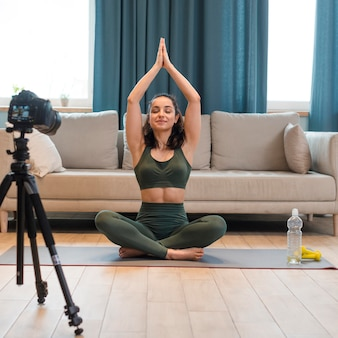 Female blogger in sportswear doing lotus pose with arms up