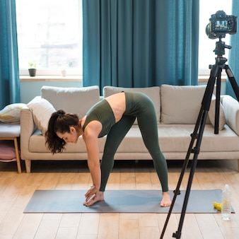 Female blogger in sportswear and stretching