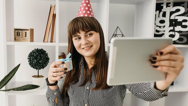 タブレットで誕生日をストリーミングする女性ブロガー
