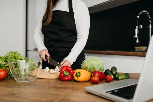 Blogger femminile streaming di cucina con il computer portatile a casa