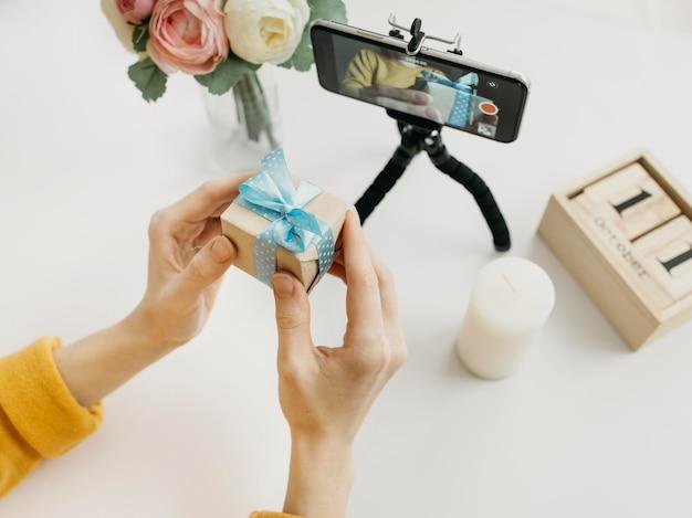 스마트 폰으로 온라인 선물을 스트리밍하는 여성 블로거