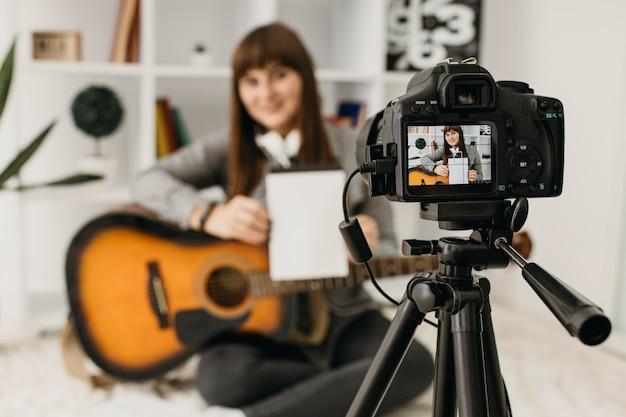 Blogger femminile streaming lezioni di chitarra a casa con la fotocamera