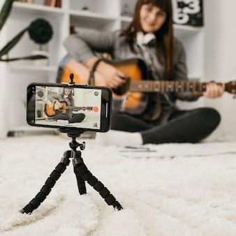 Blogger femminile streaming lezioni di chitarra con la fotocamera dello smartphone a casa