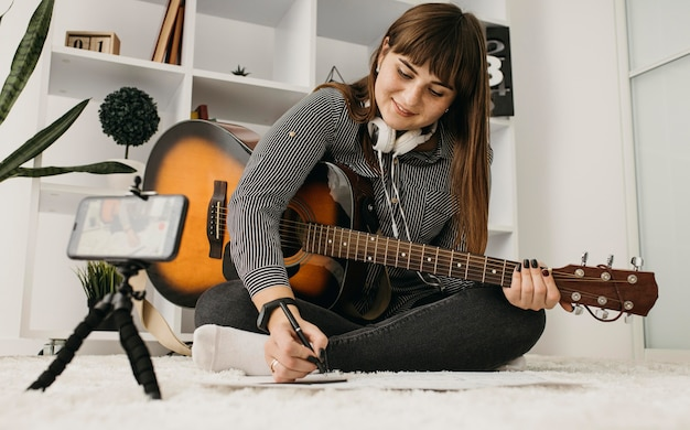 スマートフォンでギターレッスンをストリーミングする女性ブロガー
