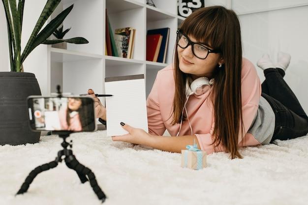 집에서 스마트 폰 및 헤드폰으로 스트리밍하는 여성 블로거