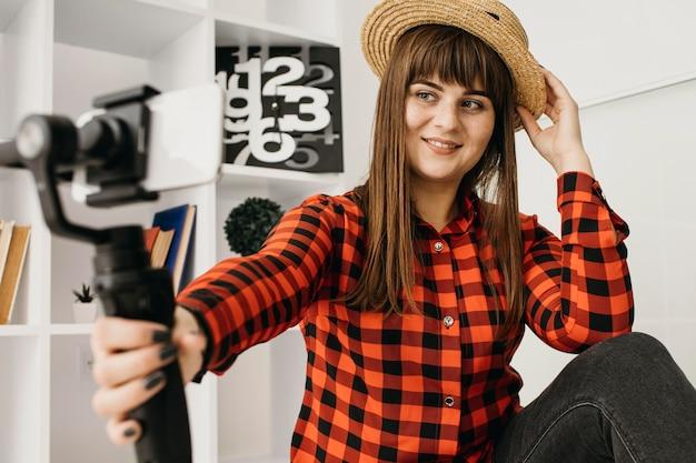 Женщина-блогер, работающая со смартфоном дома