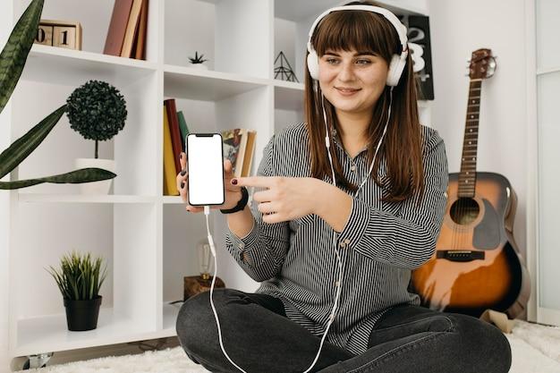 Blogger femminile in streaming con smartphone e cuffie a casa