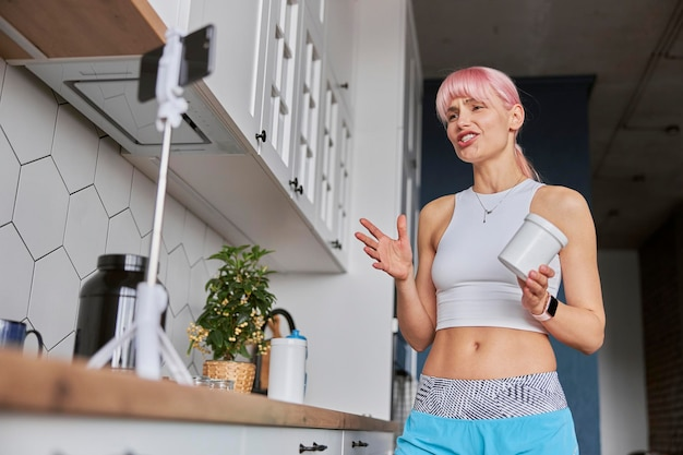 여성 블로거가 주방에서 스포츠 영양과 건강 보조 식품에 대해 이야기합니다.