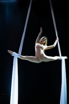 Female blond aerial performer with white aerial silks isolated on black background