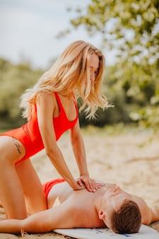 Female blond lifeguard in red bikini saving young man on the beach