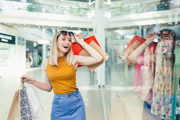 女性の金髪の買い物客は、服を着てショーウィンドウを見て、熱心に販売と割引を探しています