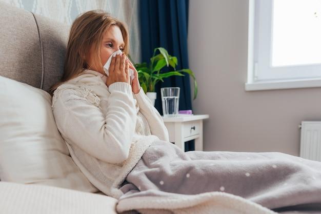 Female blows her nose holding tissue handkerchief, having symptoms of flu.