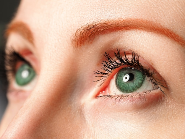 Female blue eyes tinted in green colour with special contact lens close-up