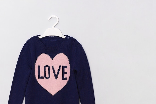 Female blue woolen sweater with pattern pink heart and inscription love on hanger on gray