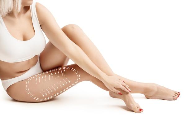 Женское тело с нанесением стрелок. концепция похудания, липосакции и удаления целлюлита. следы на женщине перед пластической операцией. изображение не ретушировано по форме тела