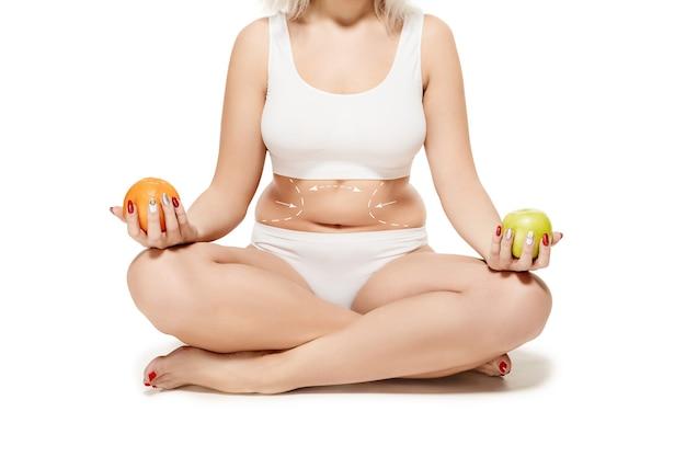 描画矢印を持つ女性の体。脂肪の喪失、脂肪吸引、セルライト除去のコンセプト。整形手術前の女性のマーク。画像はレタッチされた体型ではありません