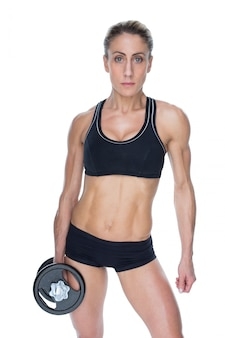 Female bodybuilder holding large black dumbbell with arm down looking at camera
