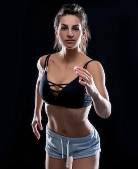 トレーニングの準備をしている身に着けている女性のボディービルダー