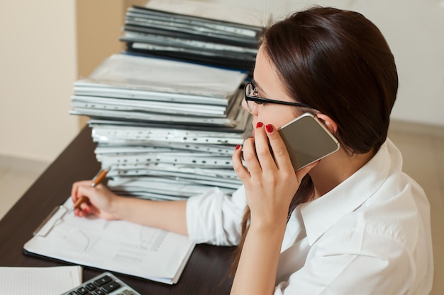 Female bookkeeper in glasses talking by phone at workplace