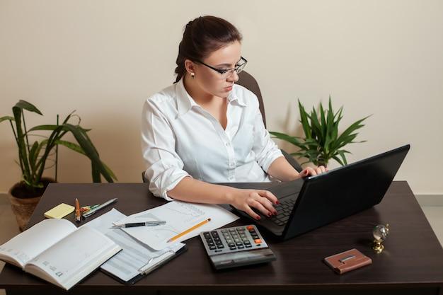 Женский бухгалтер в очках, используя ноутбук