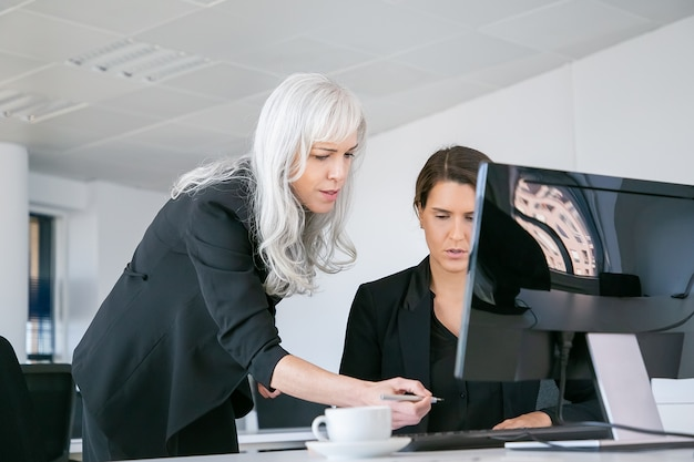 Female boss affixing signature on managers report. businesswomen sitting and standing at workplace with monitor and coffee cup. business communication concept