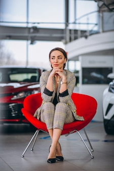 Female boss at a car showrrom sitting in a red chair