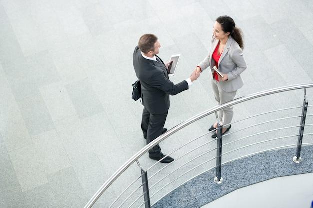 Женщина-босс пожимает руку партнеру