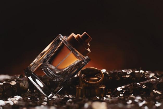 Female bottle of perfume on dark surface