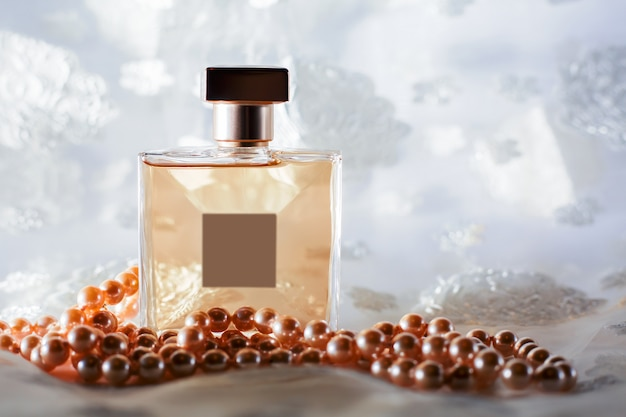 Female bottle of perfume with pearls