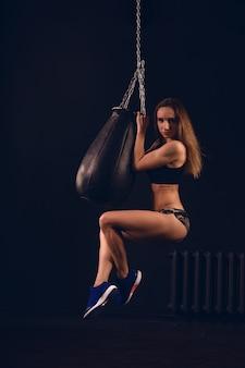 パンチングバッグからぶら下がっている女性のボクサー